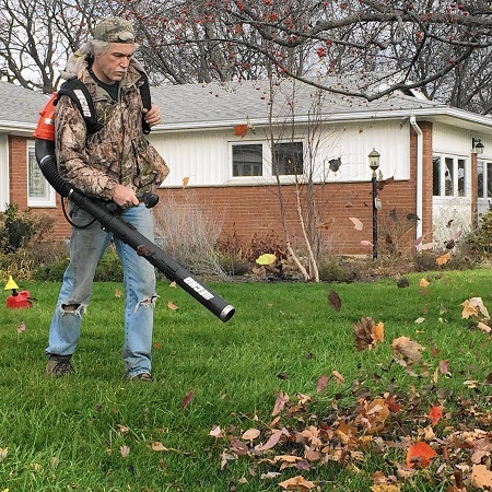 Man Using Leaf Blower In Yard